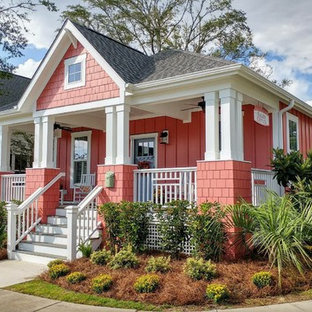 Example of a small arts and crafts red one-story concrete fiberboard house exterior design in Wilmington with a hip roof and a shingle roof