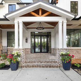 Immagine della facciata di una casa unifamiliare ampia bianca country a due piani con rivestimento in mattoni, tetto a capanna e copertura in metallo o lamiera