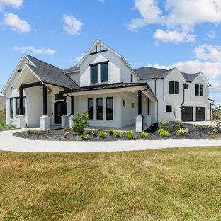 Пример оригинального дизайна: большой, двухэтажный, белый частный загородный дом в стиле кантри с облицовкой из крашеного кирпича, двускатной крышей и крышей из гибкой черепицы