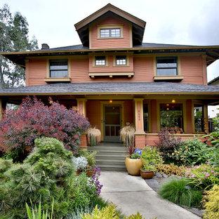 На фото: двухэтажный, оранжевый дом в стиле кантри