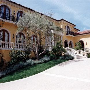 Modelo de fachada amarilla, mediterránea, extra grande, de tres plantas, con revestimiento de estuco y tejado a cuatro aguas