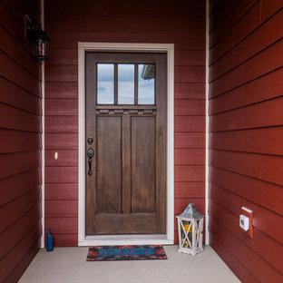Imagen de fachada de casa roja, clásica, de tamaño medio, de dos plantas, con revestimiento de aglomerado de cemento, tejado a dos aguas y tejado de teja de madera