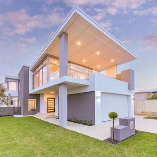 Imagen de fachada de casa multicolor, minimalista, de dos plantas, con revestimiento de estuco, tejado plano y tejado de metal
