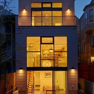 Inspiration för stora moderna beige trähus, med tre eller fler plan och platt tak