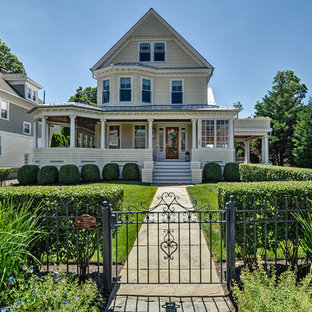 Ornate beige three-story wood exterior home photo in New York with a metal roof