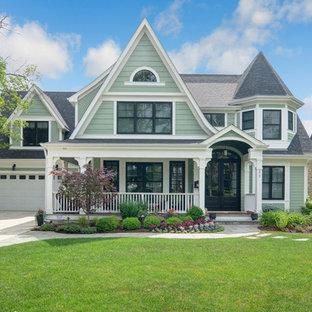 Стильный дизайн: двухэтажный, зеленый, большой частный загородный дом в викторианском стиле с комбинированной облицовкой, двускатной крышей и крышей из гибкой черепицы - последний тренд