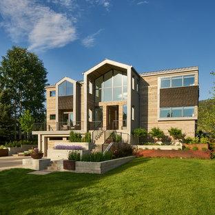 Esempio della facciata di una casa unifamiliare grande marrone contemporanea a due piani con rivestimento in legno e tetto a capanna