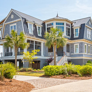 Example of a coastal gray two-story wood house exterior design in Charleston with a gambrel roof and a metal roof
