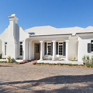 Diseño de fachada de casa blanca, marinera, de tamaño medio, de una planta, con tejado a cuatro aguas, revestimiento de hormigón y tejado de teja de barro