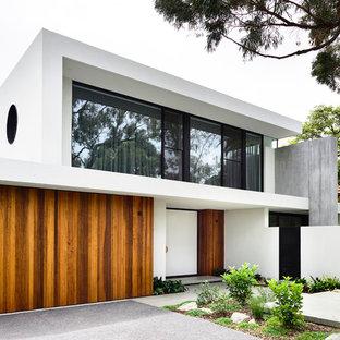 Выдающиеся фото от архитекторов и дизайнеров интерьера: двухэтажный фасад частного дома белого цвета в современном стиле с облицовкой из цементной штукатурки и плоской крышей