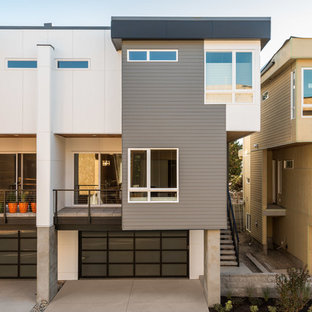 Mid-sized modern gray three-story mixed siding exterior home idea in Seattle with a metal roof