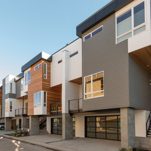 Example of a mid-sized minimalist gray three-story mixed siding exterior home design in Seattle with a metal roof