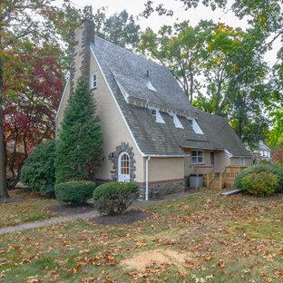 Diseño de fachada beige, clásica renovada, grande, de tres plantas, con revestimiento de estuco y tejado a doble faldón