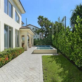 Foto de fachada de casa beige, mediterránea, de tamaño medio, de dos plantas, con revestimiento de hormigón, tejado a cuatro aguas y tejado de teja de madera