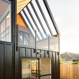 クライストチャーチの小さいモダンスタイルのおしゃれな家の外観 (メタルサイディング、黒い外壁、アパート・マンション) の写真