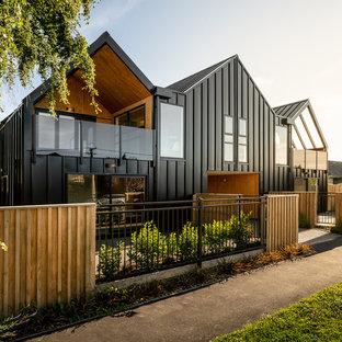 Modelo de fachada de piso negra, moderna, pequeña, de dos plantas, con revestimiento de metal, tejado a dos aguas y tejado de metal