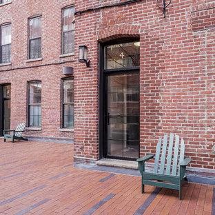 Inredning av ett industriellt mellanstort rött lägenhet, med tre eller fler plan och tegel