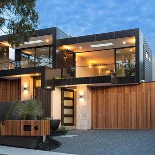 Imagen de fachada negra, contemporánea, de dos plantas, con revestimientos combinados y tejado plano