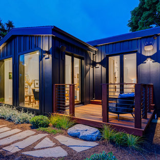 Huge trendy black one-story concrete fiberboard house exterior photo in Los Angeles with a hip roof