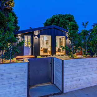 Huge contemporary black one-story concrete fiberboard house exterior idea in Los Angeles with a hip roof