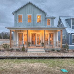 Ejemplo de fachada de casa verde, campestre, de dos plantas, con tejado a dos aguas y tejado de metal