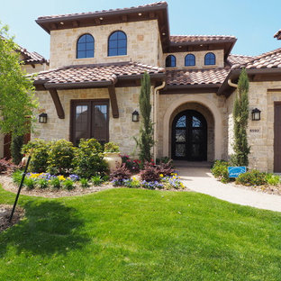 Large tuscan beige two-story stone exterior home photo in Dallas with a hip roof