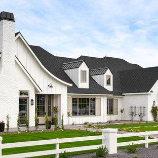 На фото: одноэтажный, белый частный загородный дом в стиле кантри с комбинированной облицовкой, двускатной крышей и крышей из гибкой черепицы