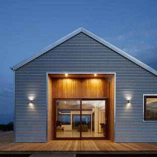 Réalisation d'une façade métallique grise nordique de taille moyenne et de plain-pied.