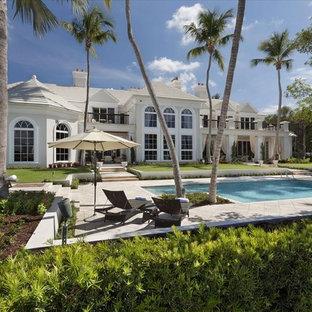 Ejemplo de fachada de casa blanca, costera, extra grande, de tres plantas, con revestimiento de adobe, tejado a la holandesa y tejado de teja de barro