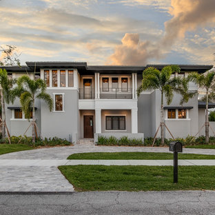 Example of an island style gray two-story house exterior design in Miami with a hip roof