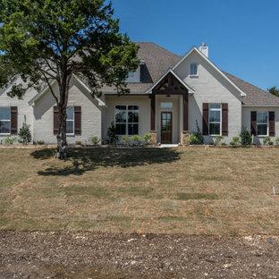 Inspiration pour une grand façade de maison blanche rustique de plain-pied et en briques peintes avec un toit à deux pans et un toit en shingle.