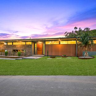 Ejemplo de fachada de casa marrón, vintage, de una planta, con revestimientos combinados y tejado plano
