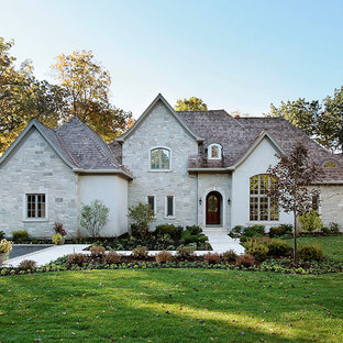 Large traditional gray two-story stone house exterior idea in Chicago with a hip roof and a shingle roof