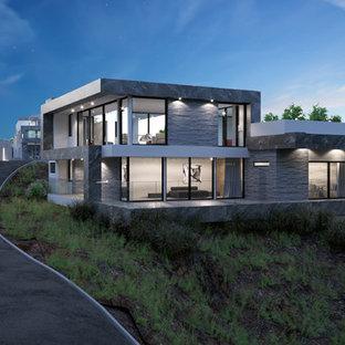 ロサンゼルスの巨大なモダンスタイルのおしゃれな家の外観 (石材サイディング、グレーの外壁、黒い屋根) の写真