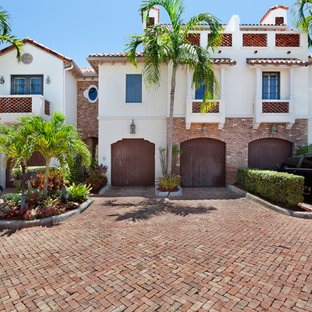 Large tropical white three-story brick townhouse exterior idea in Miami with a hip roof and a tile roof