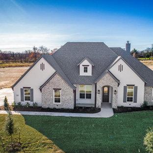 Идея дизайна: одноэтажный, белый частный загородный дом среднего размера с двускатной крышей, крышей из гибкой черепицы и облицовкой из крашеного кирпича