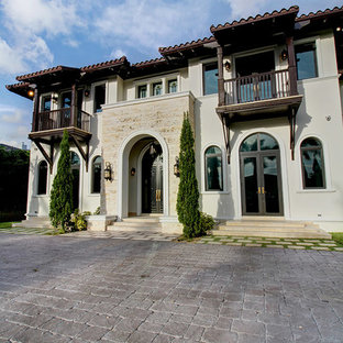 Large mediterranean white two-story stucco house exterior idea in Miami