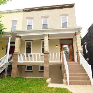 Foto de fachada amarilla, clásica, pequeña, de tres plantas, con revestimiento de ladrillo y tejado plano