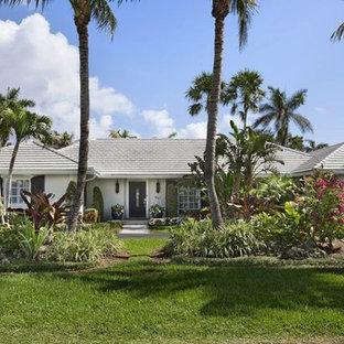 Diseño de fachada de casa multicolor, exótica, de tamaño medio, de una planta, con revestimiento de hormigón, tejado a cuatro aguas y tejado de teja de madera