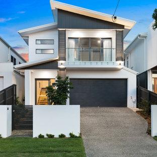 На фото: большой, двухэтажный, белый частный загородный дом в современном стиле с облицовкой из ЦСП, крышей-бабочкой и металлической крышей с