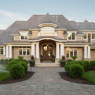 Large beach style beige two-story mixed siding exterior home idea in Minneapolis with a hip roof