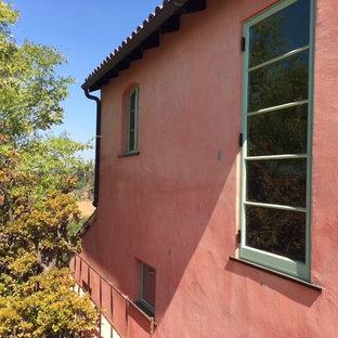 Ejemplo de fachada de casa multicolor, mediterránea, de dos plantas, con revestimiento de estuco, tejado a dos aguas y tejado de teja de barro