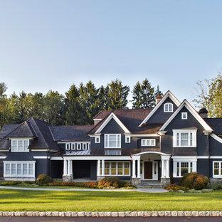 Пример оригинального дизайна: большой, трехэтажный, черный дом в классическом стиле с двускатной крышей