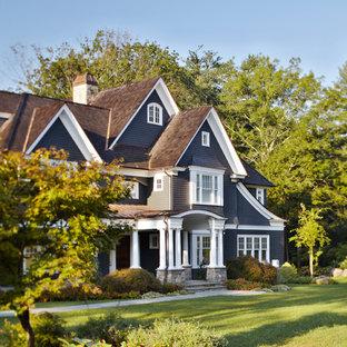 Modelo de fachada gris, tradicional, grande, de tres plantas, con revestimiento de madera y tejado a dos aguas