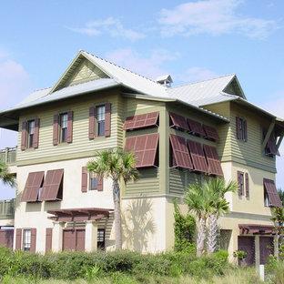 Imagen de fachada verde, exótica, grande, de tres plantas, con revestimientos combinados y tejado a dos aguas