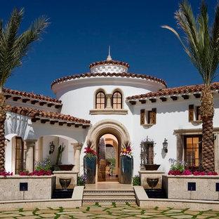 Ejemplo de fachada blanca, mediterránea, de dos plantas, con revestimiento de estuco y tejado de teja de barro