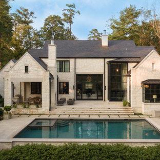 Свежая идея для дизайна: двухэтажный, бежевый частный загородный дом в стиле современная классика с облицовкой из камня - отличное фото интерьера