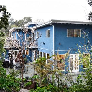Imagen de fachada de casa azul, contemporánea, de tamaño medio, de dos plantas, con revestimiento de estuco y tejado plano