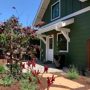 Свежая идея для дизайна: двухэтажный, деревянный, зеленый, маленький частный загородный дом в стиле кантри с двускатной крышей, крышей из гибкой черепицы, серой крышей, отделкой планкеном и входной группой - отличное фото интерьера