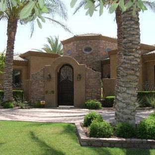 Ejemplo de fachada marrón, mediterránea, grande, de una planta, con revestimiento de estuco y tejado a cuatro aguas